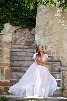 Frauenbraut sitzt auf der treppe und wartet auf ihren bräutigam. frau mit lila haaren in einem schönen hochzeitskleid