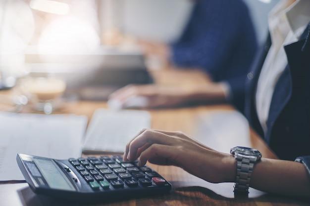 Frauenbuchhalter, der unter verwendung des rechners für berechnungsfinanzbericht am arbeitsplatz arbeitet.