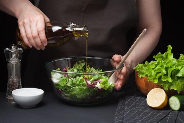 Frauenchef in der küche, die gemüsesalat zubereitet.