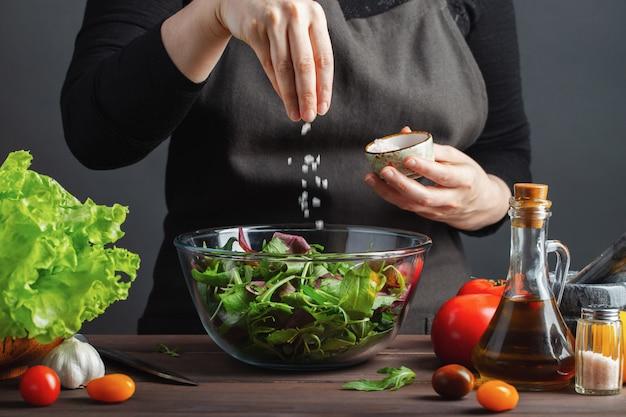 Frauenchef in der küche, die salat zubereitet.