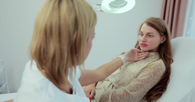 Frauendermatologe, der die lampe auf das gesicht der frau richtet, während sie die hautelastizität überprüft oder die hautuntersuchung im schönheitssalon durchführt.