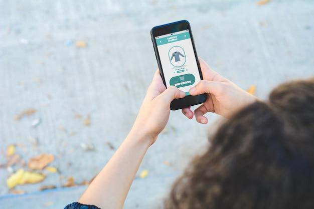 Fraueneinkaufen für kleidung auf smartphone
