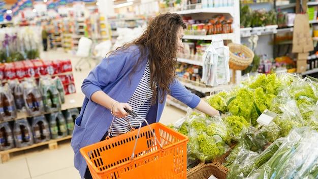 Fraueneinkaufen im supermarkt. junge frau, die aufhebt und grünen blattsalat im gemischtwarenladen wählt.