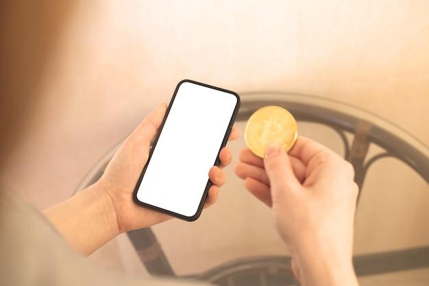 Fraueneinkaufen mit kryptomünze, mockup mit bitcoin und leerem weißen bildschirm des mobiltelefons, kopienraumfoto