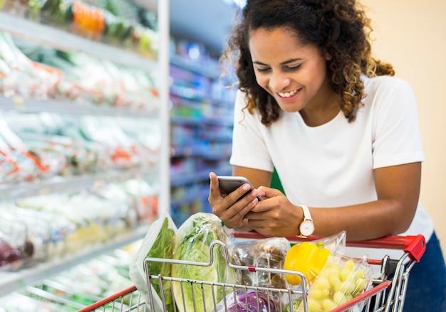 Fraueneinkaufsgemüse am supermarkt