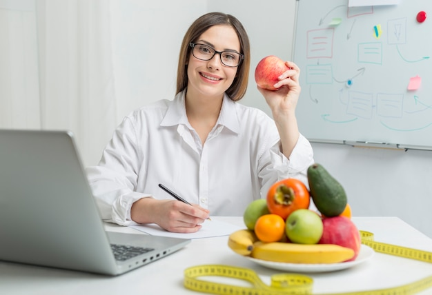 Frauenernährungswissenschaftlerdoktor, der auf dem tisch am arbeitsplatz, an den obst und gemüse sitzt.