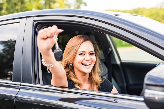 Frauenfahrer, der autoschlüssel hält, die ihr neues auto fahren lachendes junges mädchen.
