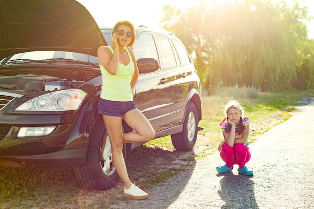 Frauenfahrer mit kind auf landstraße, nahe defektem auto.