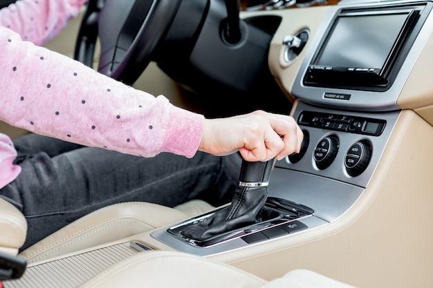 Frauenfahrerhand, die den schalthebel verschiebt