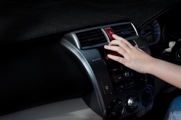 Frauenfinger, der autonotlichtknopf im auto drückt