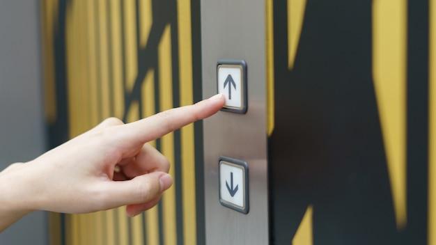 Frauenfinger, der einen aufwärtsknopf des aufzugsknopfes innerhalb des gebäudes drückt.