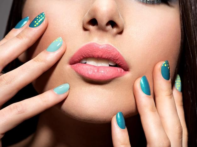 Frauenfinger mit mottonblauer farbe der nägel im gesicht