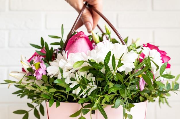 Frauenflorist, der eine schöne blumenzusammensetzung in einem blumenladen macht. frühlingsstrauß in rosa box mit griffen.