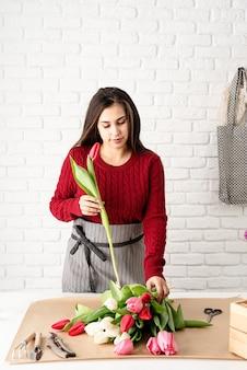 Frauenflorist, der einen blumenstrauß von frischen bunten tulpen macht
