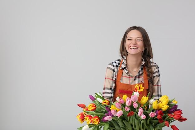 Frauenflorist, der einen blumenstrauß von tulpen zu einem feiertag vorbereitet. die bildschärfentiefe.