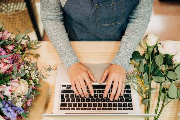 Frauenflorist, der laptop an ihrem blumenladen verwendet