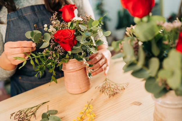 Frauenflorist macht einen blumenstrauß der roten rosen auf holztisch
