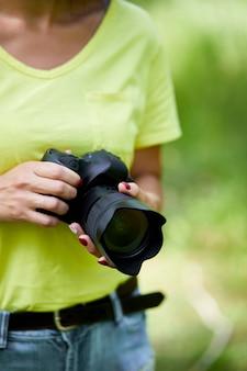 Frauenfotograf mit einer fotokamera in der hand im freien, weltfotografentag, kreatives hobby, kopierraum, platz für text, fotografiekonzepte professional.