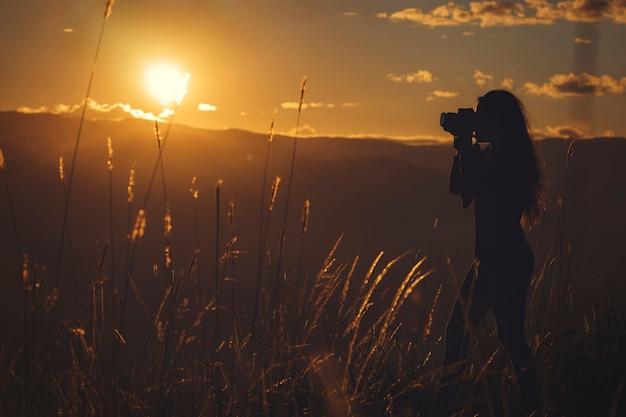 Frauenfotografin bei sonnenuntergang oben auf dem berg