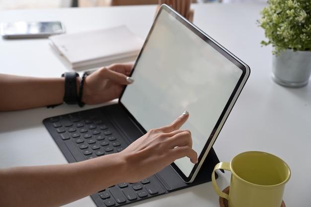 Frauenfreiberufler arbeitet an tablet-computer mit leerem kopienraumschirm für ihre werbungsgrafikanzeige