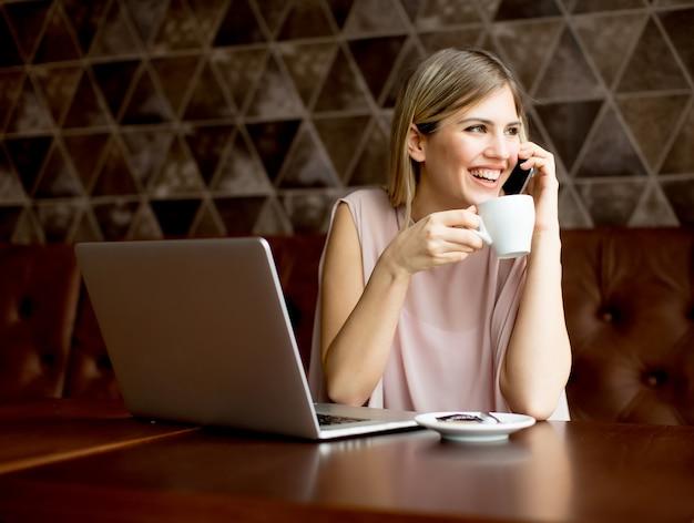 Frauenfreiberufler, der an laptop im café arbeitet und kaffee trinkt