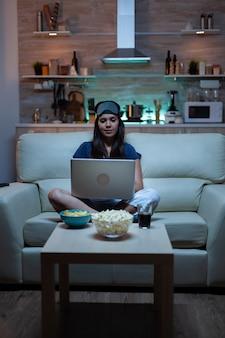 Frauenfreiberuflerin in pyjamas, die spät nachts am laptop vor dem fernseher arbeitet. glückliche person in pyjamas mit augenmaske, die auf dem sofa sitzt und schreibt, dass sie mit internettechnologie auf dem notebook surft