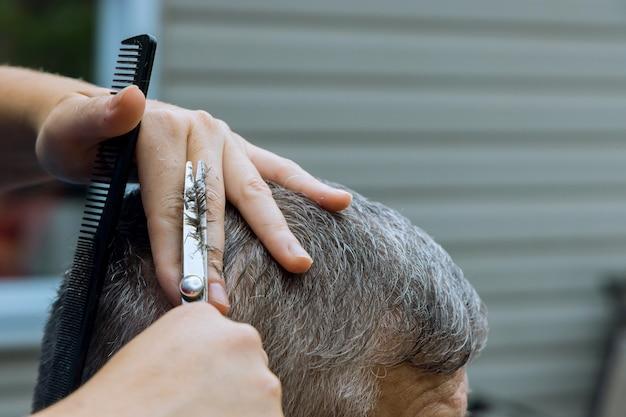 Frauenfriseur, der einem mann in einem friseur im haus die haare schneidet