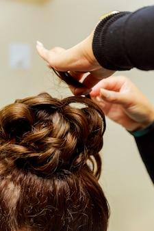 Frauenfriseur, der frisur unter verwendung des brenneisens für das lange haar der jungen frau macht