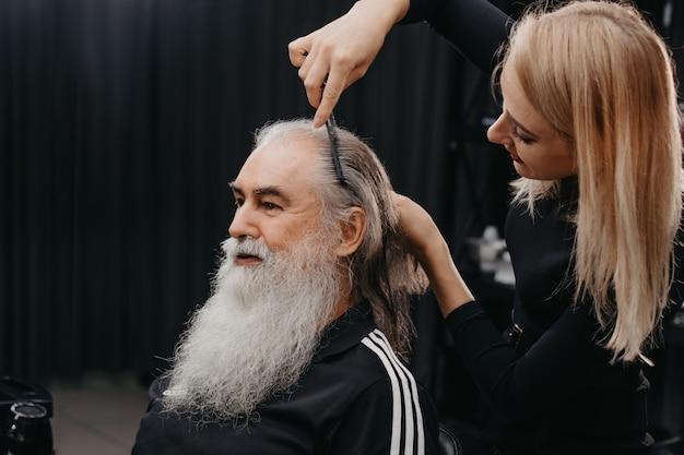 Frauenfriseur, der haare zu einem gealterten bärtigen mann kämmt