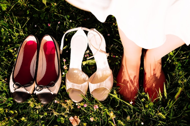 Frauenfüße auf dem gras neben fersen und ballerinas. konzept nach der arbeit barfuß im gras laufen