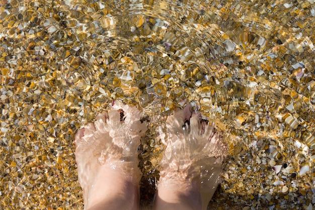 Frauenfüße auf dem hintergrund von sand und muscheln. sommerferienkonzept. urlaub am strand