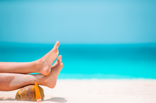 Frauenfüße auf dem weißen sandstrand im seichten wasser