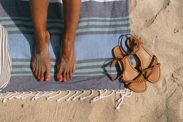 Frauenfüße auf strandtuch