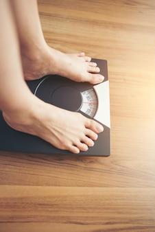 Frauenfüße, die auf gewichtsskala auf hölzernem hintergrund stehen