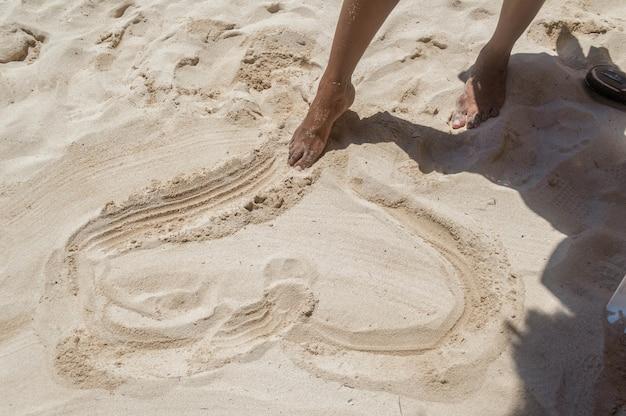 Frauenfüße, die herz im sand zeichnen. verliebte frau, die herz am strand zeichnet.