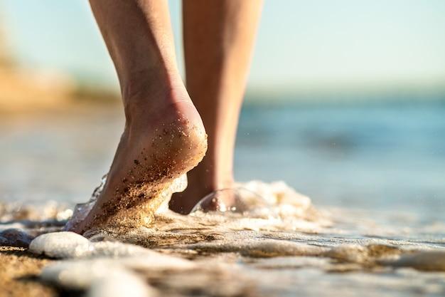 Frauenfüße gehen barfuß auf sandstrand
