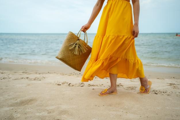Frauenfüße im gelben kleid, das auf dem meeresstrand mit tasche geht