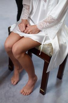 Frauenfüße im kurzen weißen kleid auf dem stuhl. gepflegte frauen beine mit pediküre in frisiermantel hautnah