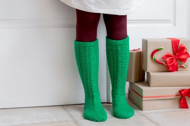 Frauenfüße in grünen socken stehen in der nähe der weißen tür mit geschenken