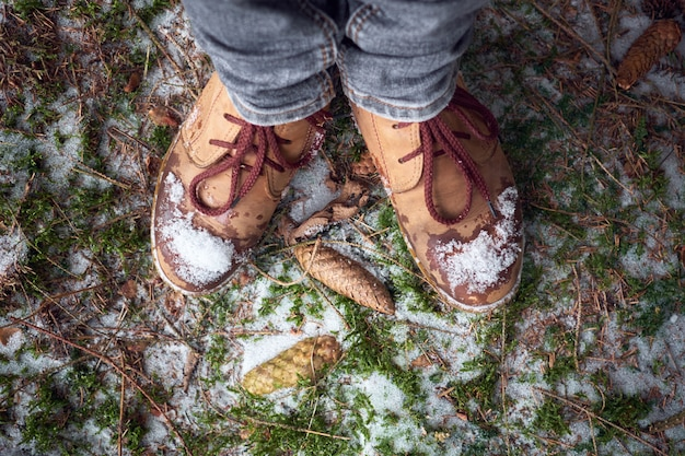 Frauenfüße in reisestiefeln auf einem moosigen schneebedeckten boden im winterwald. reisekonzept.