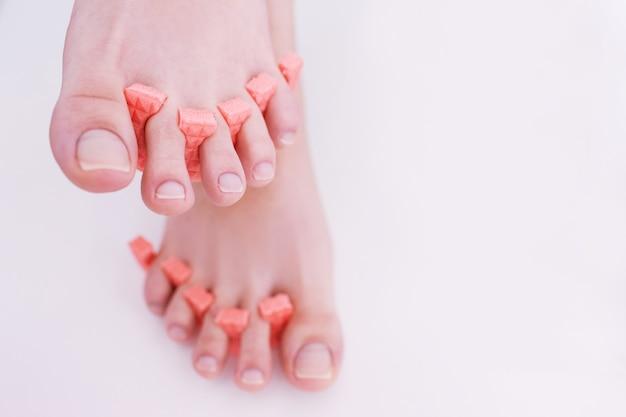 Frauenfüße mit idealer pediküre auf weißem hintergrund. schritt zum auftragen von gelpolitur. beauty-spa-verfahren im salon, nahaufnahmehintergrund