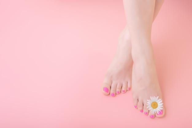 Frauenfüße mit pediküre auf nägeln und kamillenblumendekoration. hautpflegekonzept