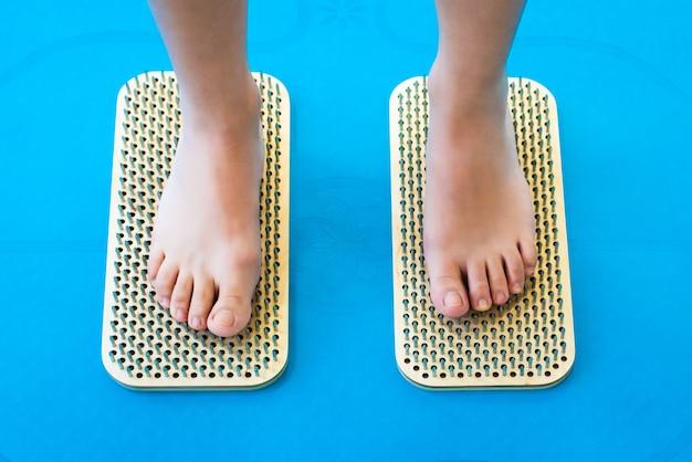 Frauenfüße stehen auf einem brett mit scharfen nägeln, sadhu board. yoga-praxis. schmerz, prüfung, gesundheit. blaue yogamatte.