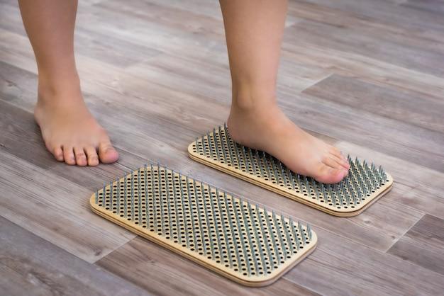 Frauenfüße stehen auf einem brett mit scharfen nägeln, sadhu board. yoga-praxis. schmerz, prüfung, gesundheit.