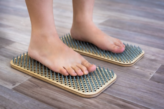 Frauenfüße stehen auf einem brett mit scharfen nägeln, sadhu board. yoga-praxis.