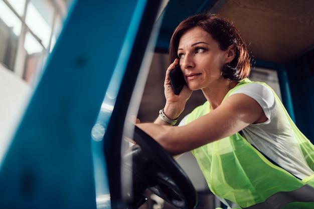 Frauengabelstaplerfahrer, der am telefon im fahrzeug spricht