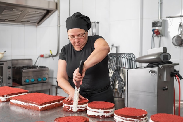 Frauengebäckchef, der glücklich lächelt und arbeitet und kuchen an der konditorei macht.