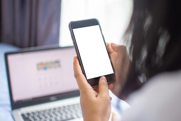 Frauengebrauch smartphone für internet und mit laptop online kaufen. weicher fokus.