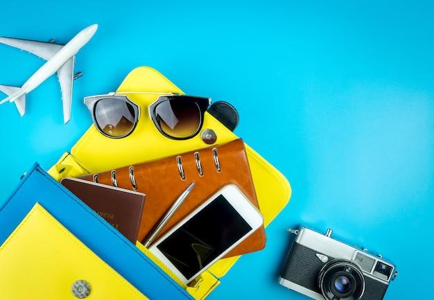 Frauengeldbeutel mit reisezubehör mit spielzeugflugzeug auf blauem hintergrund