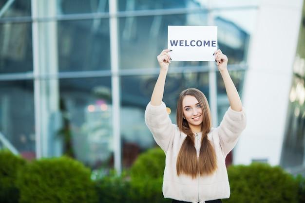 Frauengeschäft mit dem plakat mit willkommensmitteilung